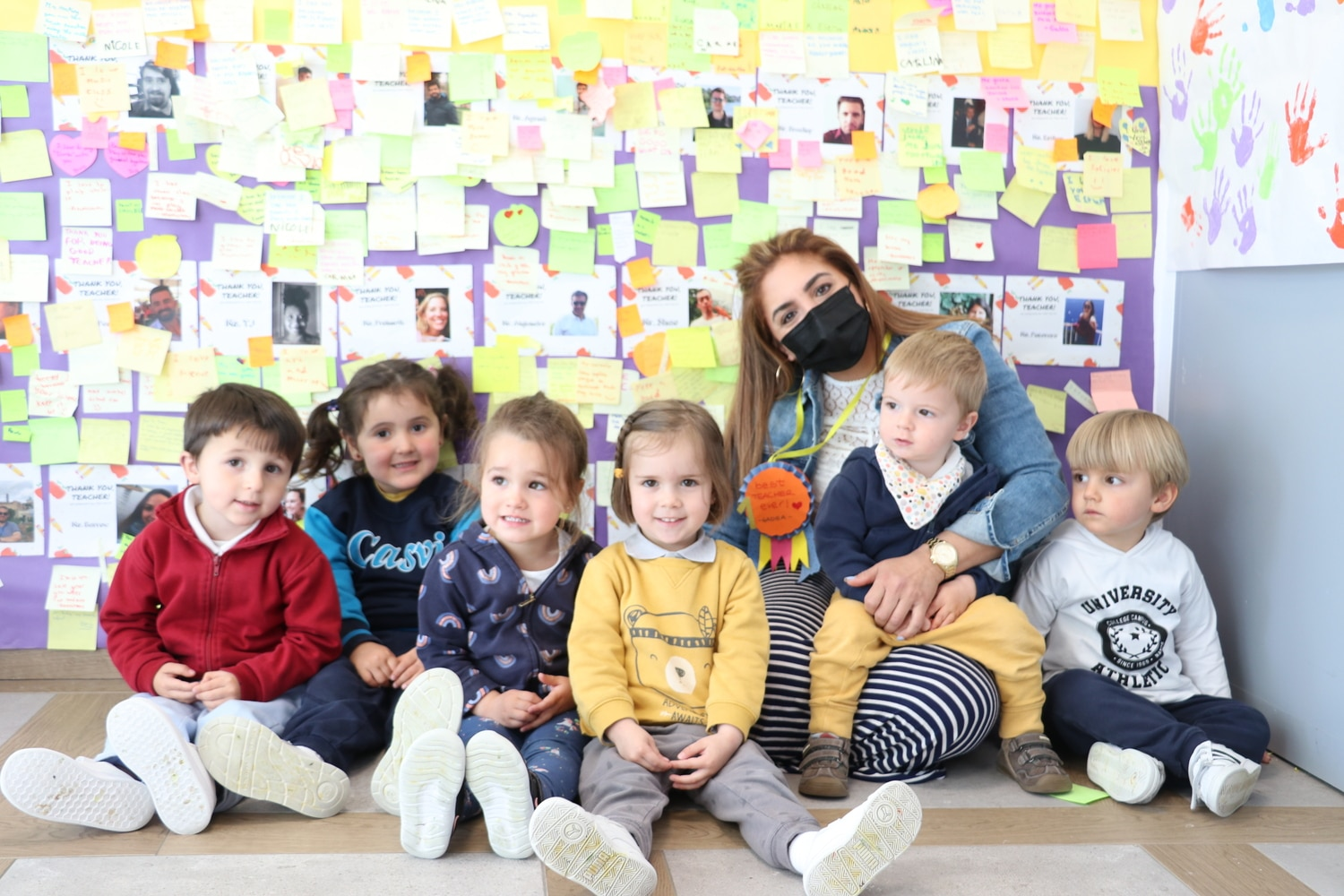 a group of Nursery students are taking a picture iun the wall of appreciation