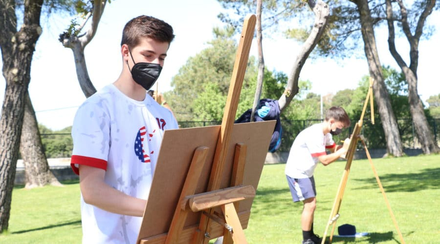 students are painting surrounded by nature in the playground